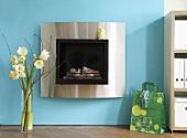 A fireplace set into a blue wall (Design: Yvonne van de Straat)