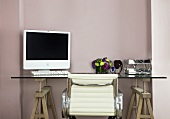 A work table with a computer resting on top of wooden saw horses and a white leather office chair in front of a pastel colored wall