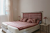 Two beds next to each other with a red and white checked quilt