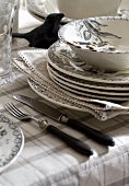 A stack of plates and cutlery on a table cloth