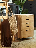 Rolling file cabinet out of wood with drawers and shopping basket hanging on a chair