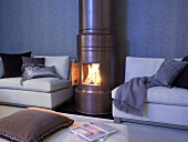 A copper coloured wood burning stove with a open door and view of the fire next to a sofa strewn with pillows and throws
