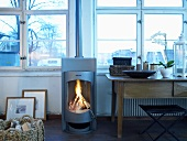 Stainless steel wood burning stove with fire next to a wooden table in front of a wall of windows
