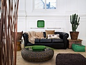 Rattan floor table in front of a black leather couch and cactus pot in a living room