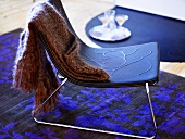 Wool shawl on a stool with blue seat and stainless steel frame on a black and blue carpet with floral pattern