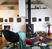 Living room under a ceiling with lounge chair and side table in front of a wood burning stove