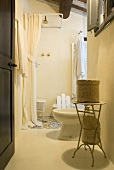 Open door with a view into a bathroom with a table with baskets and shower with white shower curtain