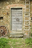 Ladder and wooden wheel in front of a natural stone facade with a wooden door