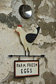 Farmhouse fresh eggs -- 'For Sale' sign with an animal figure on a natural stone facade