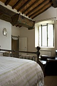 Rustic bedroom under a wooden timber beam ceiling