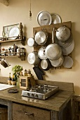 Gas stove on a rustic wooden working area and cooking utensils hanging on a wooden board