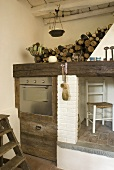 Corner of a kitchen with built-in stainless steel oven in a rustic wooden cabinet next to a chimney and a place to store firewood
