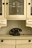 White crockery cupboard with old fashioned telephone