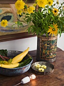 Metal containers with flowers and vegetables on a wooden shelf