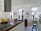 White designer kitchen - stainless steel vent over a countertop with a wooden working area and window wall