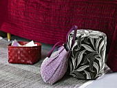 Red basket and bag next to an upholstered stool in front of a bed with a red bedspread