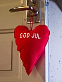 Red, heart shaped pillow hanging on a door
