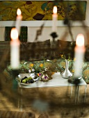 View through hanging candlesticks onto a metal table with flower vases