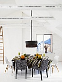 White attic with chairs in a mix of styles at a dining table and black hanging lamp