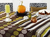 Candle light, pumpkin and cake on a tablecloth with many different designs