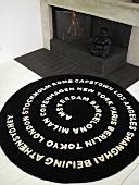 weiße Schrift auf schwarzem Teppich vor offenem Kamin