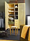 Rattan wardrobe with open door and wicker stool
