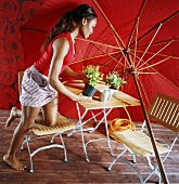 A side shot of a woman kneeling on a garden chair with a flower pot in her hand in front of a red sun umbrella