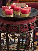 Burning, red candles with gold stripes on a black tray and upholstered stool