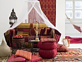 Oriental-themed sitting area with cushions around a side table and hookah