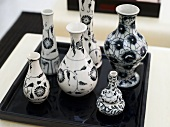 Collection of vases with a black-and-white design on a black tray