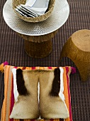 Pillows with hide covers and rustic stool with a shiny white dish