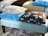 Solid color and patterned pillows on an upholstered bench