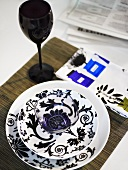 Glass bowl decorated with a black and white design and black stemware on a placemat
