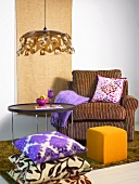 Cozy reading chair with a yellow upholstered foot stool and stack of pillows in front of a side table