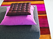 Pillows in assorted shades of red on a gray pad and striped carpet