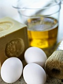 Three white chicken eggs in front of a bar of soap and a filled measuring jug