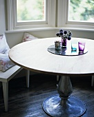 A round table in front of a window seat