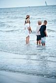 Vier Kinder stehen im Meer