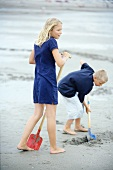 A girl and a boy digging on the beach