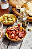 Dried tomatoes, olives and olive oil on a garden table