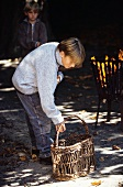 Young boy standing next to a basket next to an open fire
