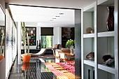 Wohnraum in Designerstil eingerichtet, Liege, orangefarbener Pflanzentopf, schwarzer glänzender Fussboden
