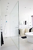 A white bathroom with a shower area separated by a glass wall and contrasting black towels