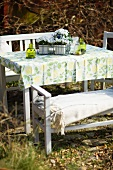 A white table and chairs with a floral patterned tablecloth and flowers in a garden