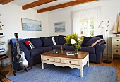 A living room in a country house - a blue guitar next to a white coffee table and a sofa