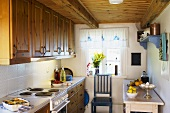 A kitchen in country house with wooden cupboard and a wooden ceiling