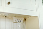 Electrical outlet under a kitchen cabinet with white doors