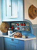 A kitchen counter with a blue wooden front and integrated preserving jars