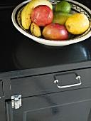 A bowl of fruit on a shelf