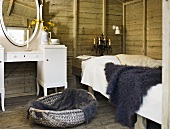 A rustic room with wooden walls - a fur on a bed and a white make-up table